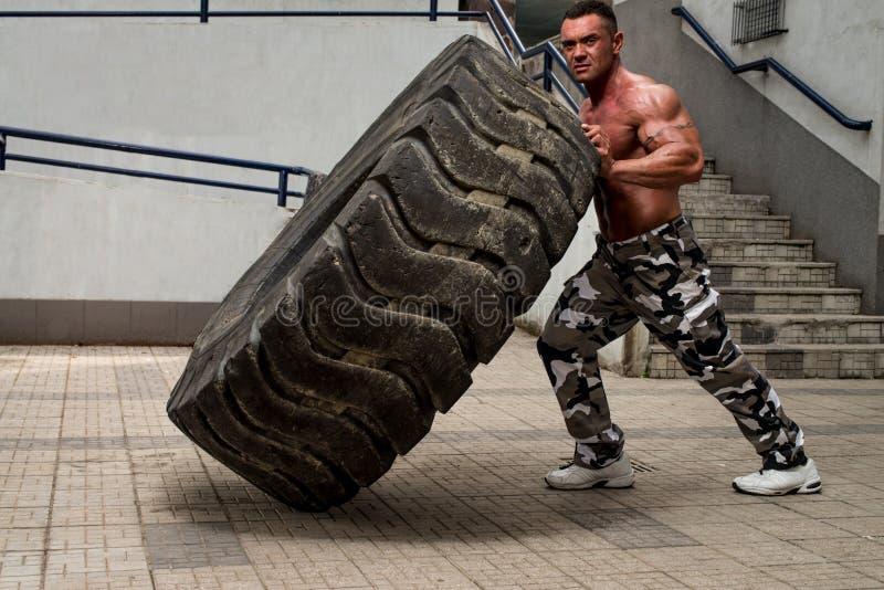 Um homem muscular que participa em um exercício apto da cruz fazendo uma aleta do pneu imagem de stock