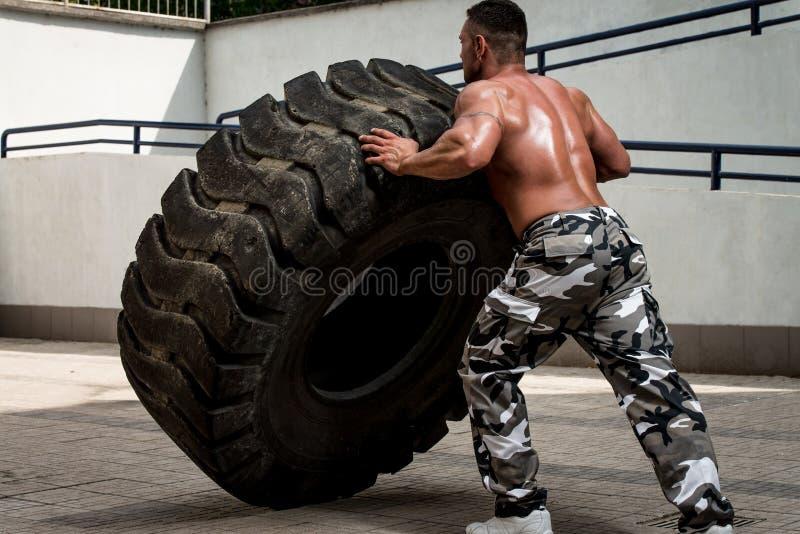 Um homem muscular que participa em um exercício apto da cruz fazendo uma aleta do pneu imagens de stock royalty free