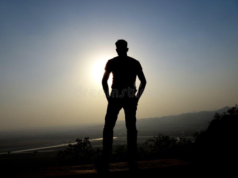 Um homem não identificado que está sobre um pico de montanha na altura da fotografia da silhueta do por do sol, liberdade do mont fotografia de stock royalty free