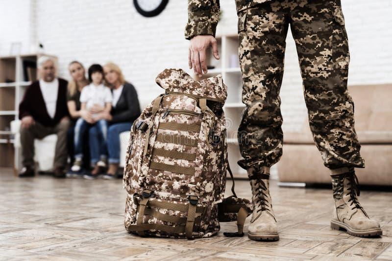 Um homem na camuflagem com uma trouxa militar sae da casa fotos de stock royalty free