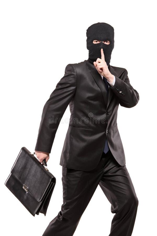 Um homem na máscara da extorsão que rouba uma pasta fotografia de stock royalty free