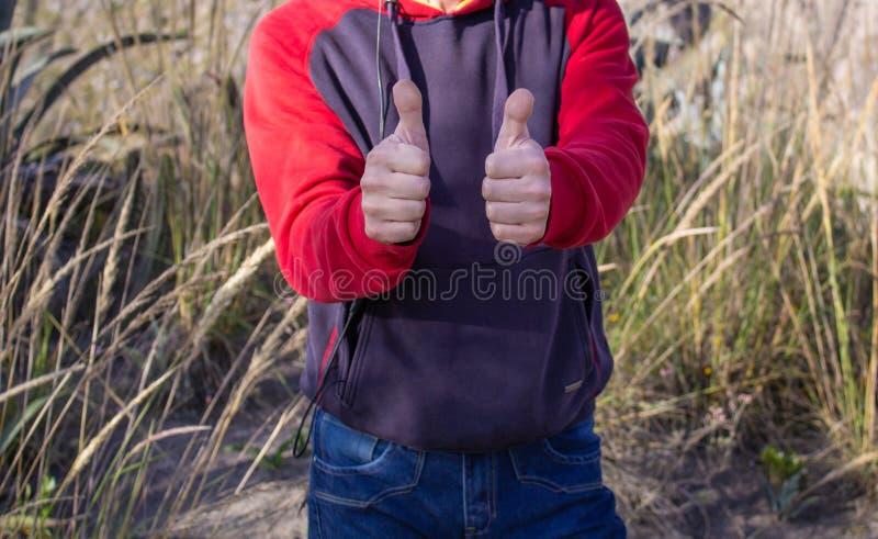 Um homem na natureza na pradaria Mostra dois polegares fotografia de stock royalty free