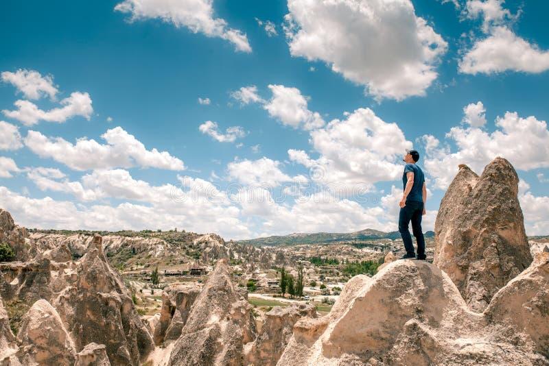 Um homem na parte superior de um monte em Cappadocia em Turquia olha acima às nuvens surpreendentes Curso, sucesso, liberdade, re fotos de stock