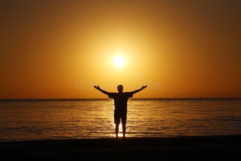 Um homem na praia dá boas-vindas ao nascer do sol As mãos são espalhadas distante imagem de stock