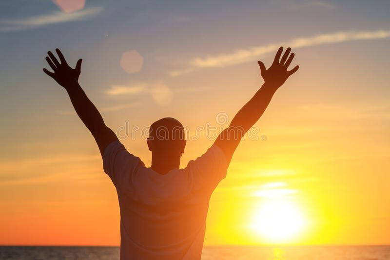 Um homem na praia no por do sol mostra a suas mãos como feliz é com o conceito do curso e do abrandamento imagens de stock