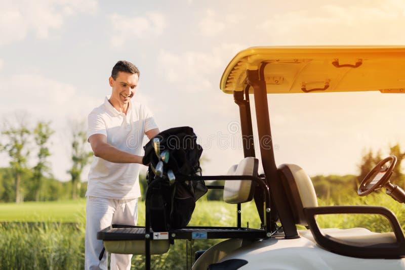 Um homem na roupa branca empilha um saco com os clubes de golfe no tronco de um carrinho de golfe foto de stock