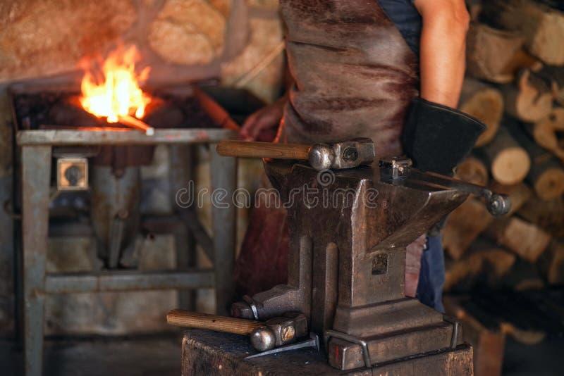 Um homem na roupa de trabalho trabalha com metal Um homem guarda um martelo e um metal quente em sua mão imagens de stock royalty free