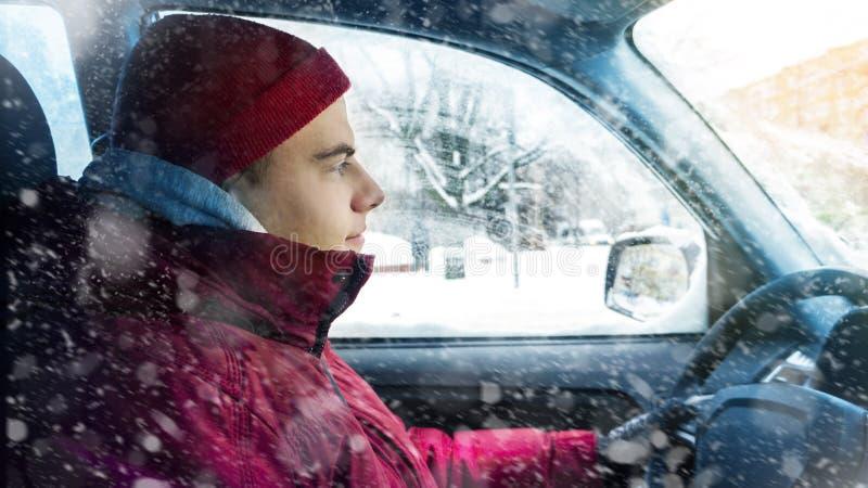 Um homem na roupa do inverno conduz um carro no inverno fotografia de stock royalty free