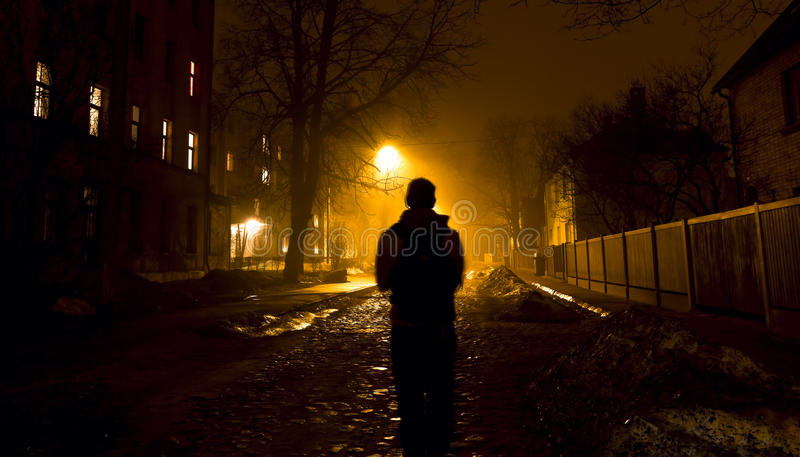 Um homem na rua nevoenta na noite foto de stock