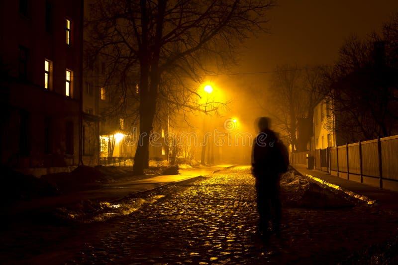 Um homem na rua nevoenta na noite fotografia de stock royalty free