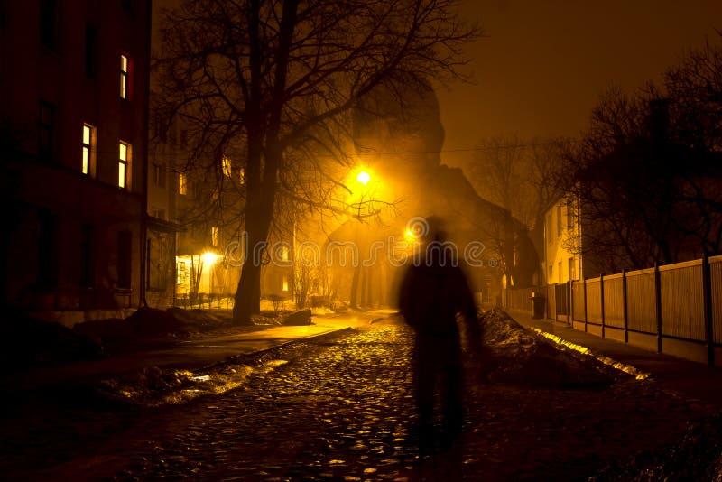 Um homem na rua nevoenta na noite foto de stock royalty free