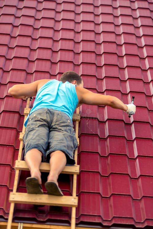 Um homem nas escadas com reparos de um martelo a coberta de telhado imagens de stock royalty free