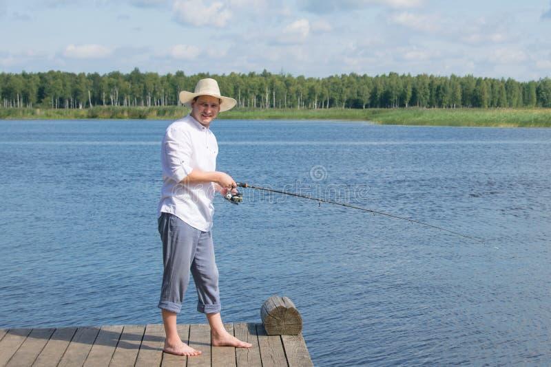 Um homem no cais, em um chapéu branco, mantendo uma vara de pesca para pescar, contra o lago e o céu azuis imagens de stock royalty free