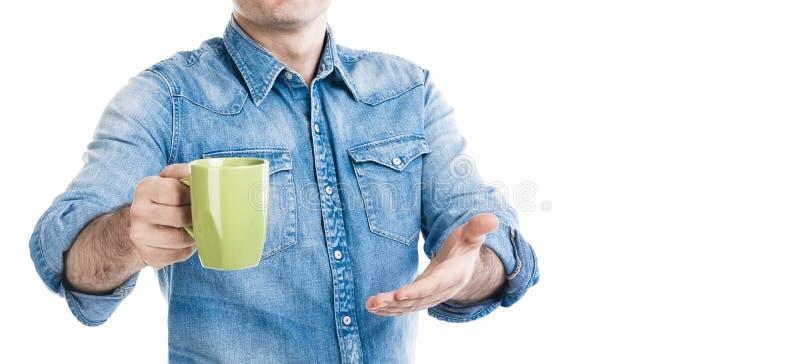 Um homem no desgaste do estilo ocasional que sugere a xícara de café Convide o cliente a provar Nenhuma cara, bandeira do close u imagens de stock