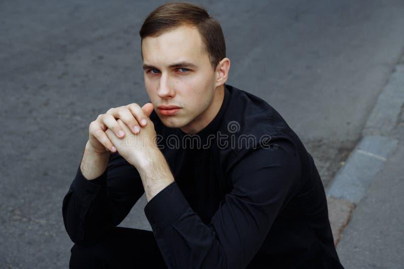 Um homem no preto com um chapéu negro está sentando-se no asfalto na rua, na estrada imagem de stock
