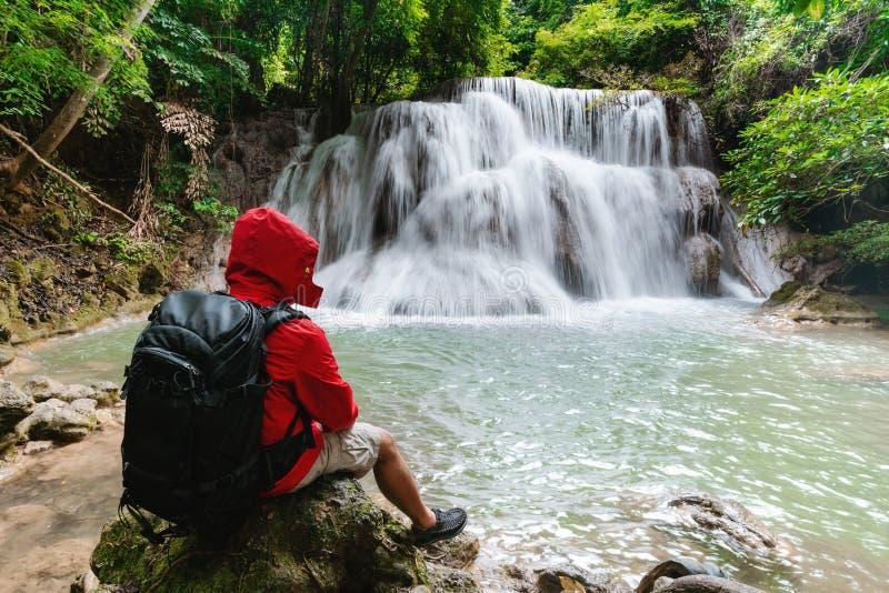 Um homem no revestimento vermelho com a trouxa que senta-se na rocha que aprecia a cachoeira bonita na floresta tropical tropical fotos de stock