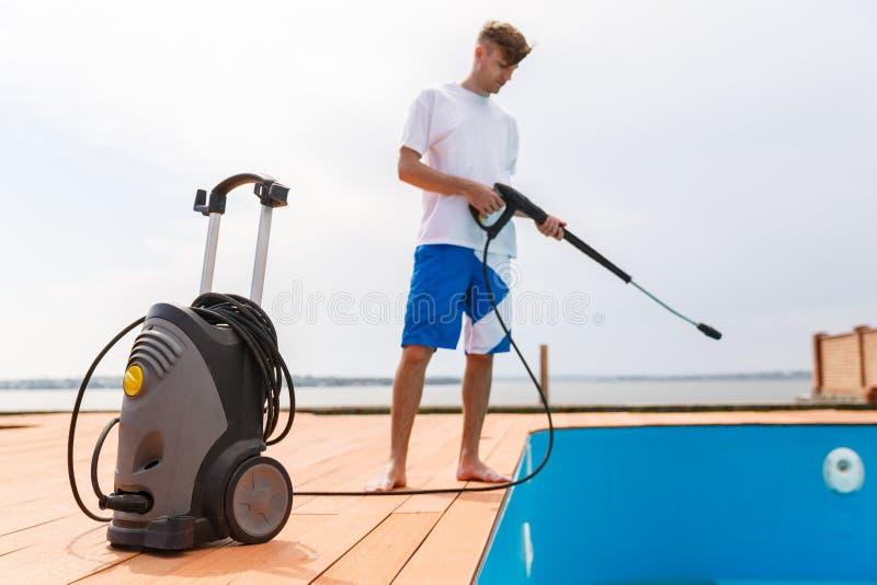 Um homem no short azul limpa uma piscina fotos de stock royalty free