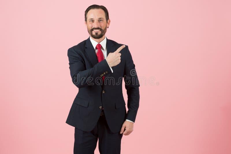 Um homem no terno azul mostra o sentido a acima no fundo cor-de-rosa O indivíduo farpado com sorriso faz a venda e a propaganda fotografia de stock