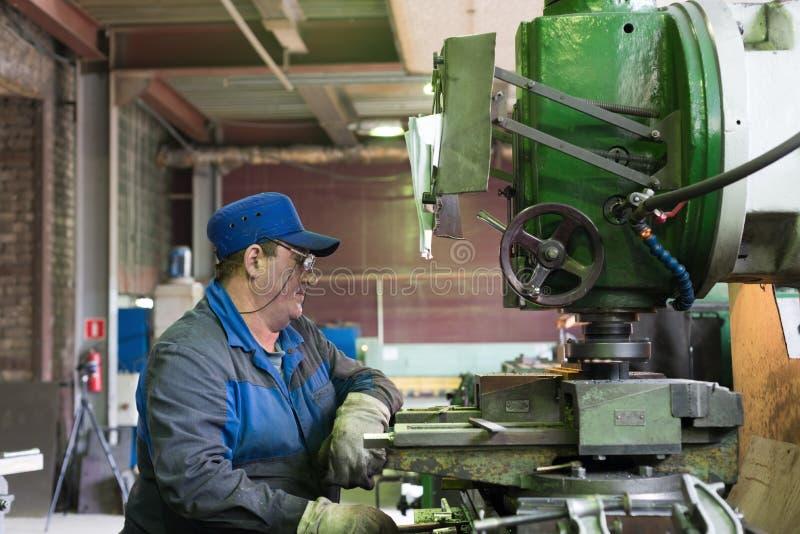 Um homem no trabalho em uma máquina de trituração vertical Fazer à máquina de uma peça de metal em uma máquina do metal-corte foto de stock royalty free