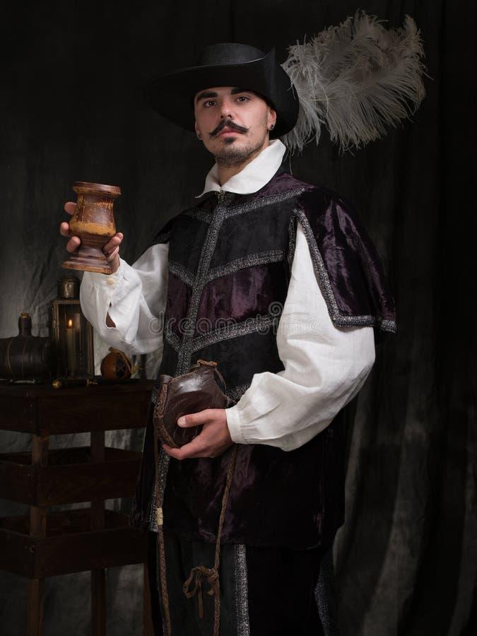 Um homem no traje e no chapéu de período aumenta um vidro do vinho imagem de stock royalty free