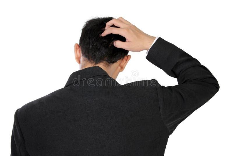 Um homem no vestuário formal que risca sua cabeça na confusão, isolada no branco foto de stock royalty free