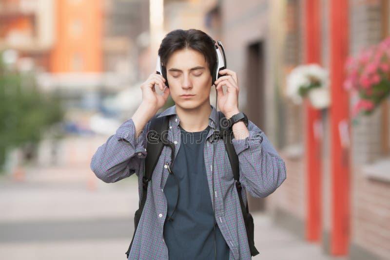 Um homem nos fones de ouvido escuta a música Tien Shan imagem de stock