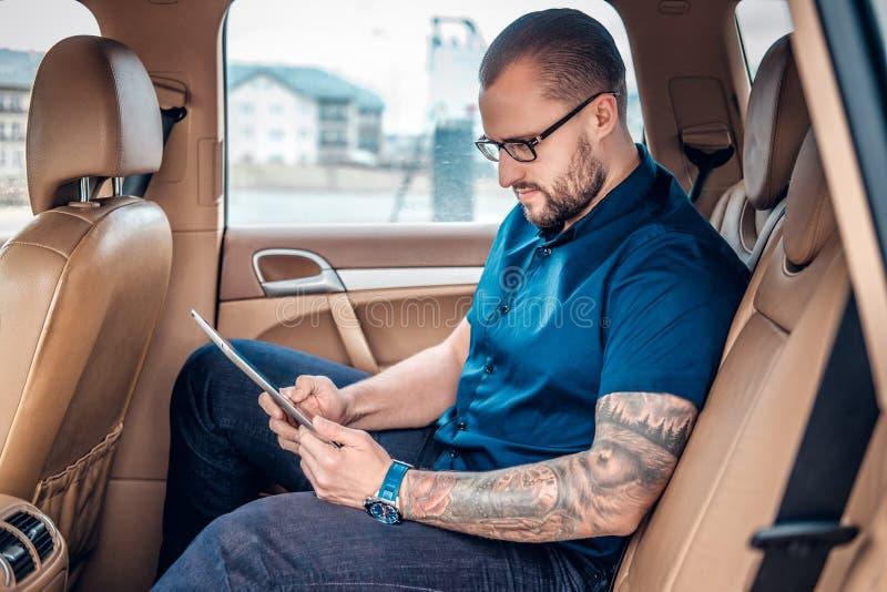 Um homem nos monóculos com tatuagem em seu braço usando o PC portátil da tabuleta em um banco traseiro de um carro fotografia de stock royalty free