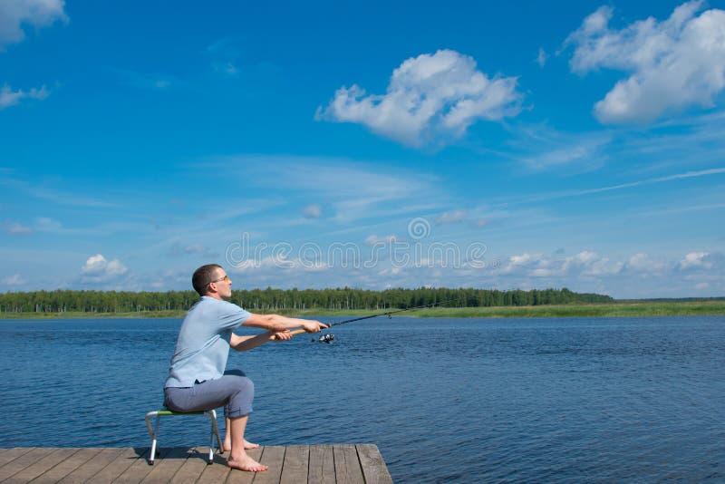 Um homem nos vidros amarelos, sentando-se no cais, contra uma paisagem bonita, joga uma vara de pesca no lago para travar peixes foto de stock