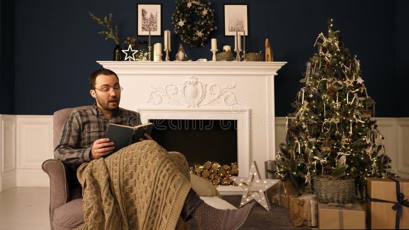 Um homem nos vidros na cadeira que lê um livro em casa no tempo do Natal para fora ruidosamente Iterior do Natal foto de stock royalty free