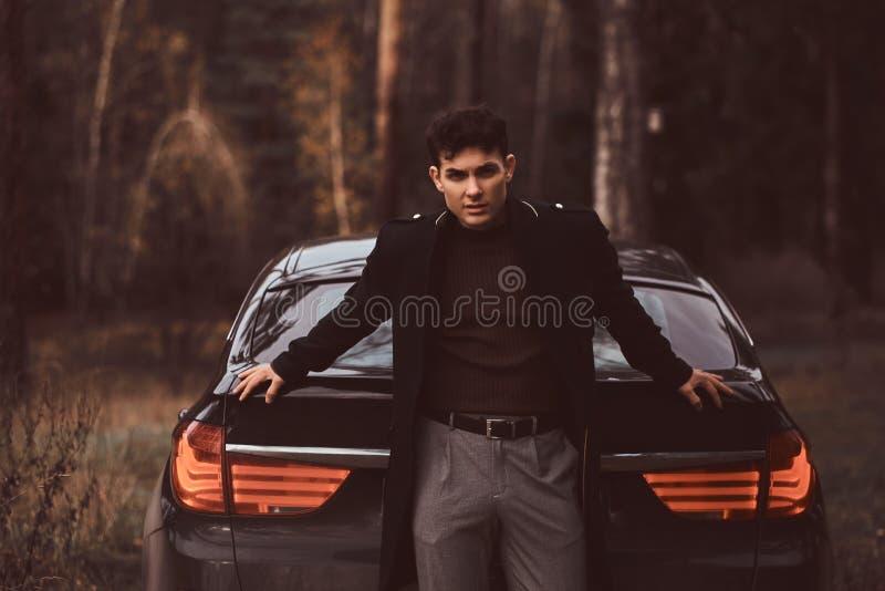 Um homem novo à moda que veste um revestimento preto que inclina-se em um carro luxuoso na floresta do outono imagens de stock royalty free