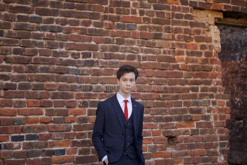 Um homem novo, um adolescente, em um terno clássico Meditar está estando na frente da parede velha do tijolo vermelho, pondo suas imagem de stock