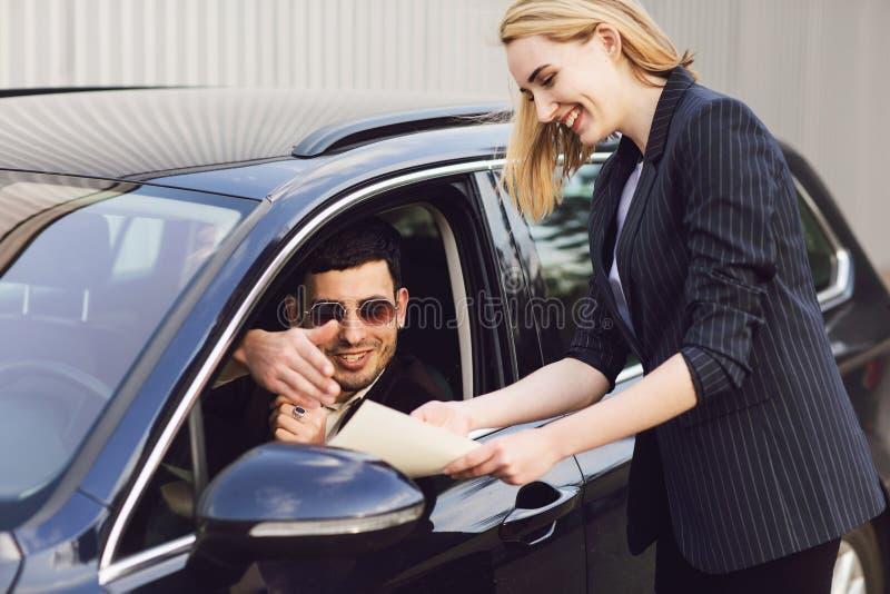 Um homem novo aluga um carro O empregado do centro do negociante mostra documentos perto do carro imagem de stock royalty free