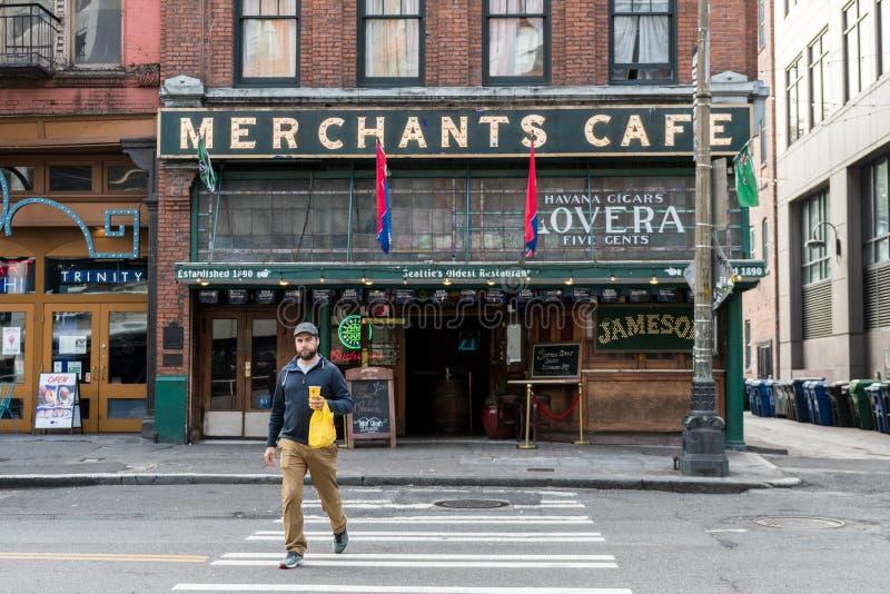 Um homem novo anda na frente do café dos comerciantes, a barra a mais velha em Seattle, Washington, EUA fotografia de stock royalty free