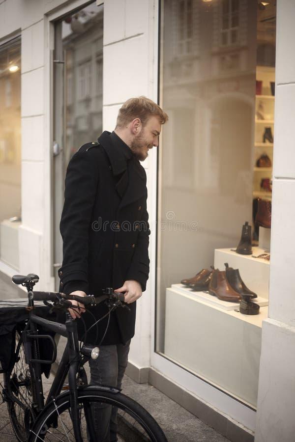 Um homem novo, 20-29 anos velho, comprando sapatas extravagantes estando na frente de uma loja com sua bicicleta, olhando a uma l imagem de stock