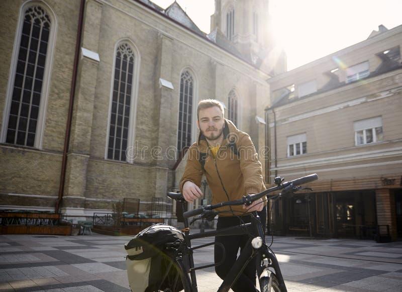 Um homem novo, 20-29 anos velho, levantando com sua bicicleta em um quadrado de cidade bonito em Europa, Sérvia, Novi Sad foto de stock royalty free