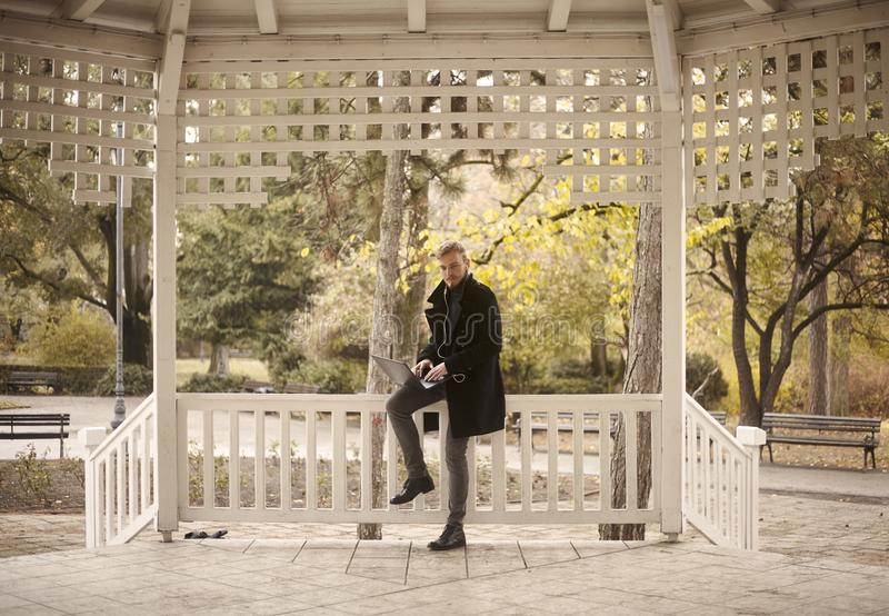 Um homem novo, 20-29 anos velho, sentando-se na cerca fora no parque, ao usar seu port?til fotos de stock royalty free