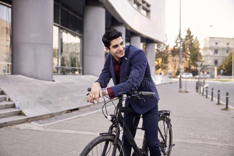 Um homem novo, 20-29 anos velho, terno vestindo, olhando lateralmente, sorrindo levantando na bicicleta extravagante da cidade, i imagem de stock