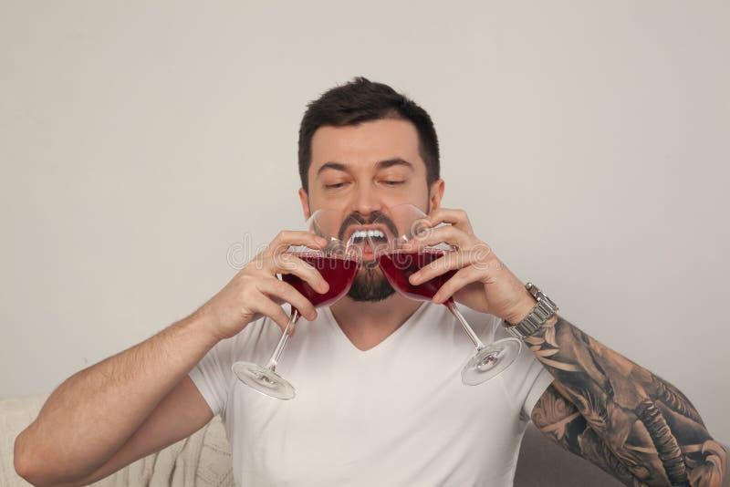Um homem novo bebe o vinho de dois vidros na frente de um fundo branco, ele é vestido em um t-shirt branco foto de stock