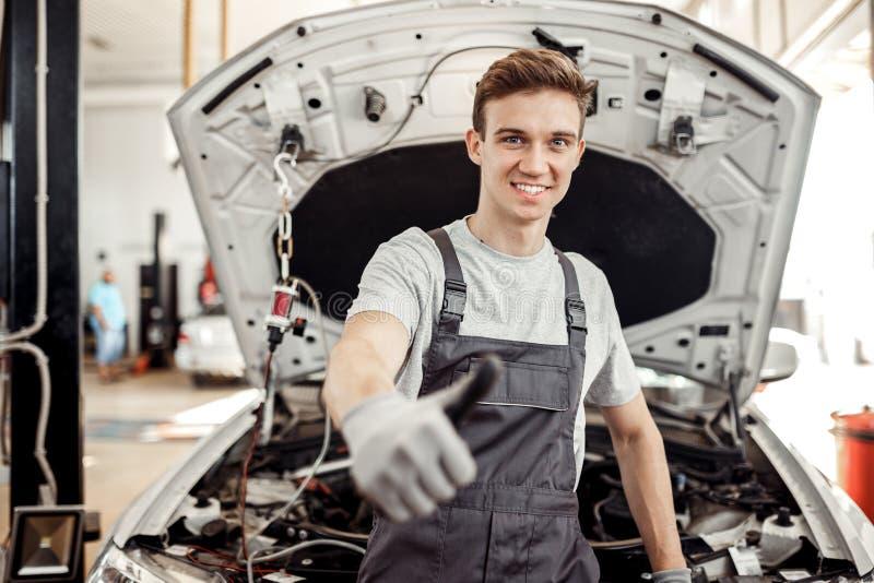 Um homem novo bonito está em seu trabalho: serviço de reparações do carro fotos de stock royalty free