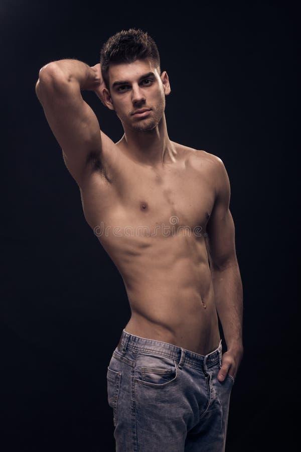 Um homem novo, calças de brim descamisado do corpo apto do Abs fotos de stock