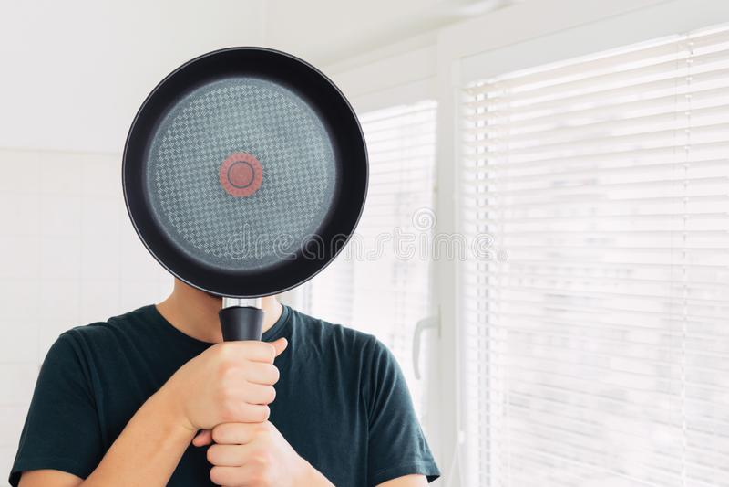 Um homem novo cobre sua cara com uma frigideira imagens de stock royalty free