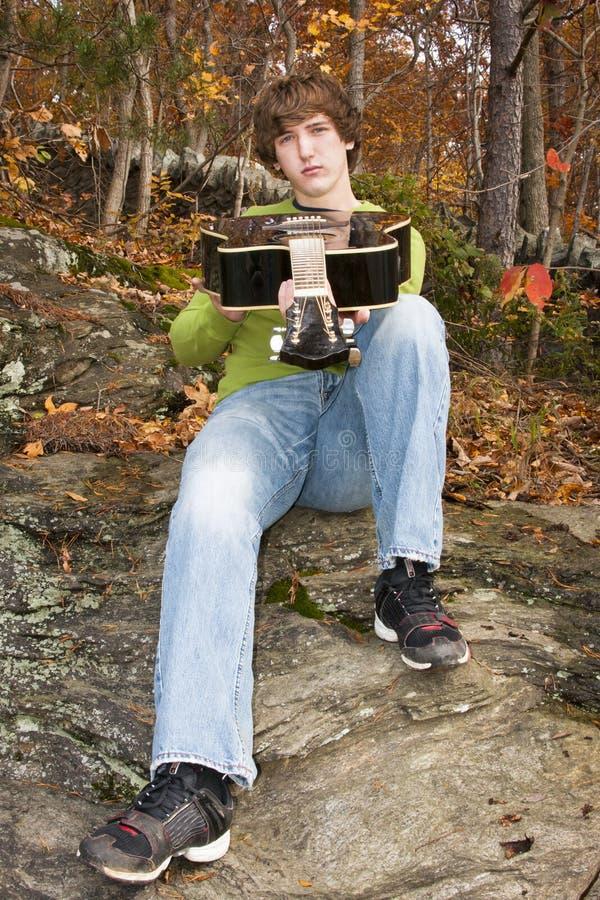 Um homem novo com sua guitarra nas madeiras do outono foto de stock royalty free