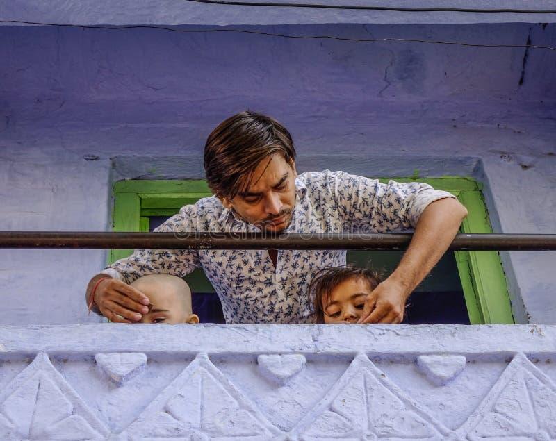 Um homem novo com suas crianças na casa rural imagem de stock