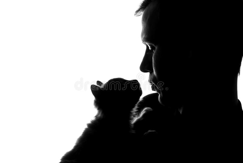 Um homem novo com um gatinho em suas mãos imagens de stock