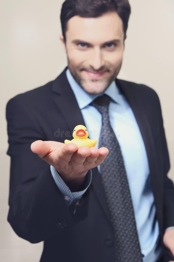 Um homem novo com um pato de borracha amarelo imagens de stock royalty free