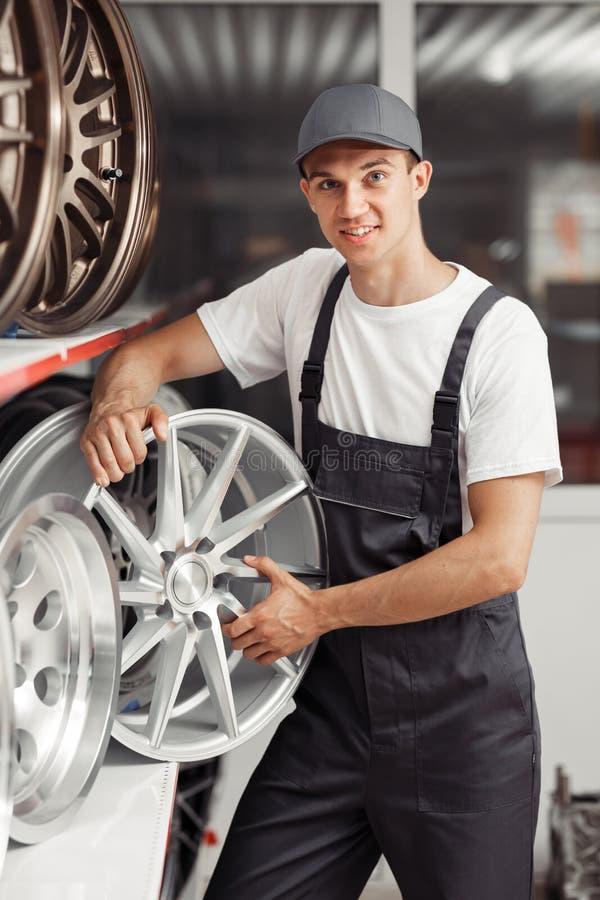 Um homem novo com uma borda do pneu em suas mãos está estando perto das prateleiras foto de stock