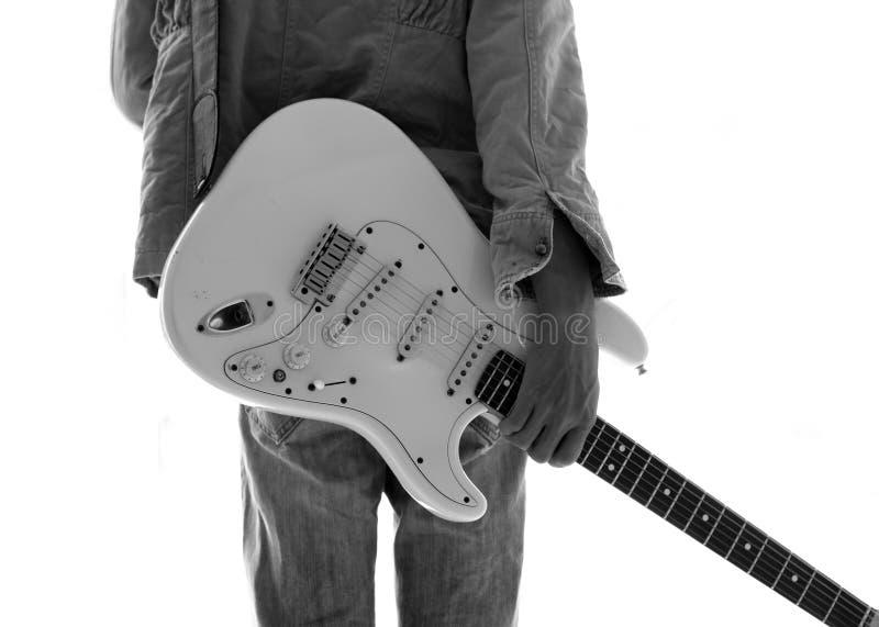 Um homem novo com uma guitarra elétrica que inclina-se contra um wa do cimento imagens de stock royalty free