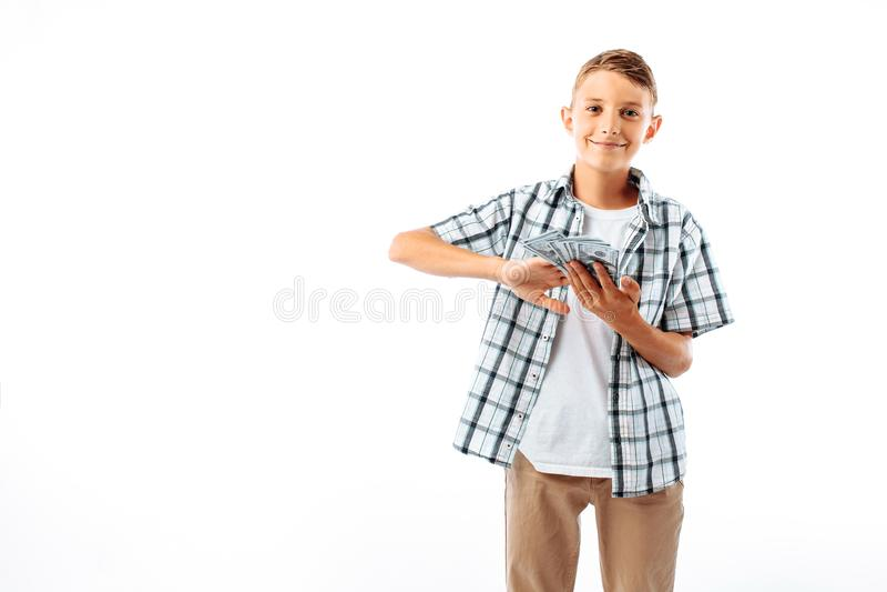 Um homem novo com vidros joga cem contas de dólares, um retrato de um adolescente bem sucedido em uma camisa no estúdio em um b b fotografia de stock