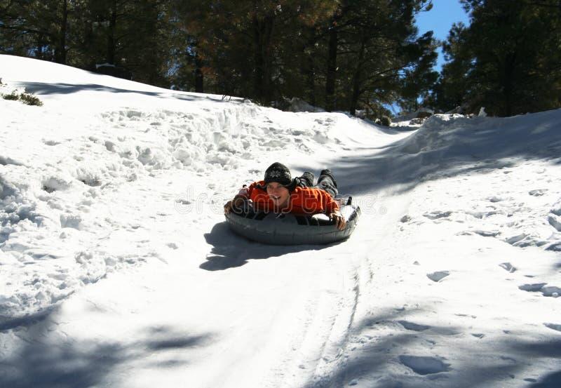 Um homem novo compete abaixo de um monte nevado no inverno fotos de stock royalty free