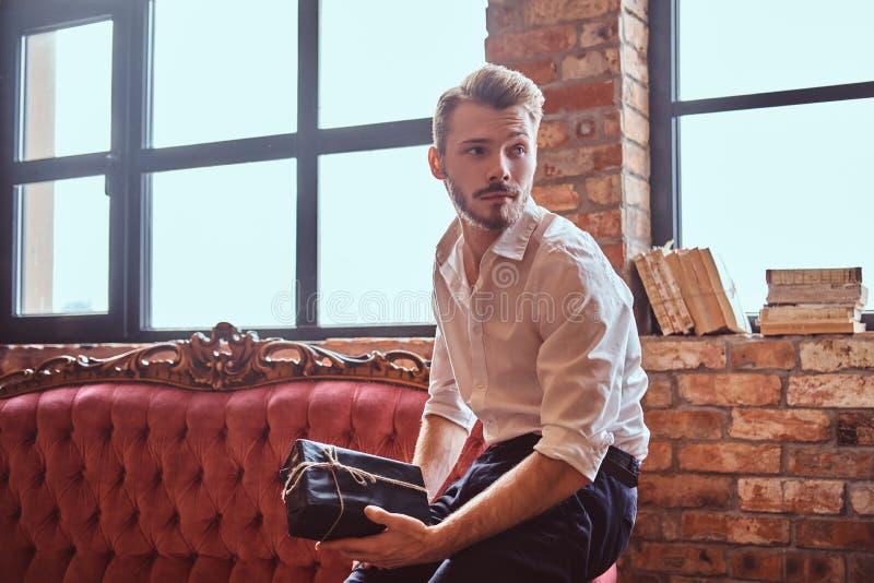 Um homem novo considerável com uma barba e um cabelo à moda vestiu elegantemente guardar uma caixa de presente ao sentar-se em um imagem de stock